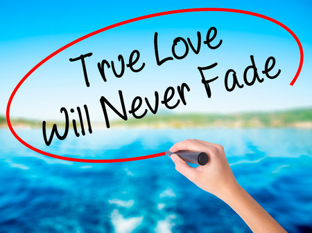 Woman Hand Writing True Love Will Never Fade on blank transparent board with a marker isolated over water background. Business concept. Stock Photo Stock Photo