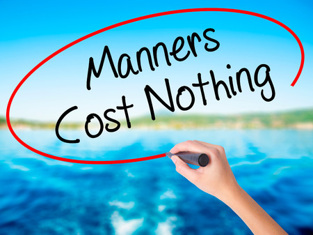 Woman Hand Writing Manners Cost Nothing on blank transparent board with a marker isolated over water background. Business concept. Stock Photo