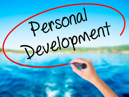 Woman Hand Writing Personal Development  on blank transparent board with a marker isolated over water background. Business concept. Stock Photo