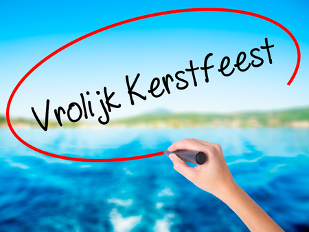 Woman Hand Writing Vrolijk Kerstfeest  (Happy Christmas in Dutch) on blank transparent board with a marker isolated over water background. Business concept. Stock Photo Stock Photo