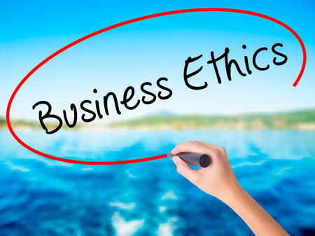 Woman Hand Writing Business Ethics on blank transparent board with a marker isolated over water background. Business concept. Stock Photo