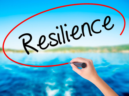 Woman Hand Writing Resilience on blank transparent board with a marker isolated over water background. Business concept. Stock Photo