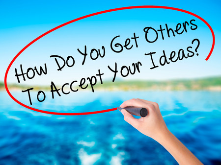 Woman Hand Writing How Do You Get Others To Accept Your Ideas? on blank transparent board with a marker isolated over water background. Business concept. Stock Photo Stock Photo