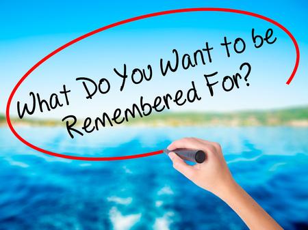 Scrittura a mano da donna Cosa vuoi essere ricordato? a bordo trasparente bianco con un pennarello isolato su sfondo di acqua. Concetto di business Foto d'archivio Archivio Fotografico