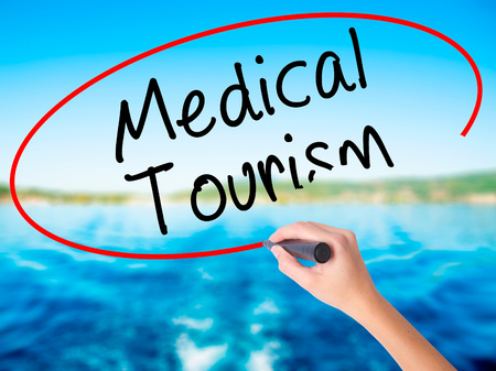 health care fees: Woman Hand Writing Medical Tourism on blank transparent board with a marker isolated over water background. Business concept. Stock Photo