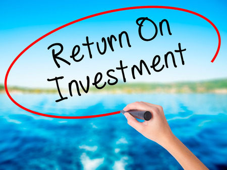 rate of return: Woman Hand Writing Return On Investment  on blank transparent board with a marker isolated over water background. Business concept. Stock Photo