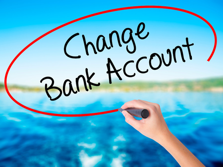 Woman Hand Writing Change Bank Account on blank transparent board with a marker isolated over water background. Business concept. Stock Photo