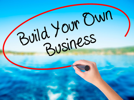 Woman Hand Writing Build Your Own Business with a marker over transparent board. Isolated on background. Business, technology, internet concept. Stock  Photo