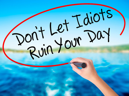 stupidity: Woman Hand Writing Dont Let Idiots Ruin Your Day on blank transparent board with a marker isolated over water background. Business concept. Stock Photo