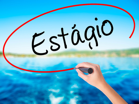 Woman Hand Writing Est????'Â?gio (Internship in Portuguese)  on blank transparent board with a marker isolated over water background. Business concept. Stock Photo