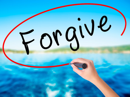 Woman Hand Writing Forgive on blank transparent board with a marker isolated over water background. Business concept. Stock Photo