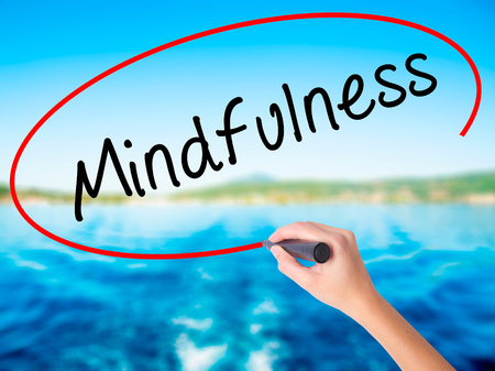 Woman Hand Writing Mindfulness  on blank transparent board with a marker isolated over water background. Business concept. Stock Photo Stock Photo