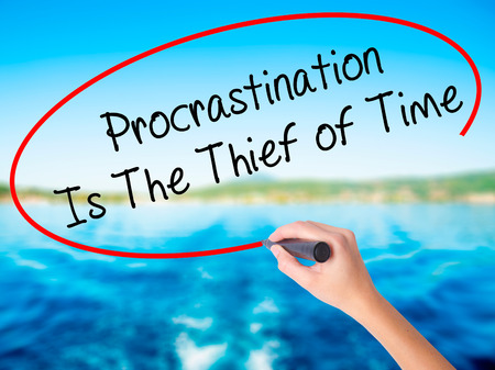 Woman Hand Writing  Procrastination Is The Thief of Time on blank transparent board with a marker isolated over water background. Business concept. Stock Photo