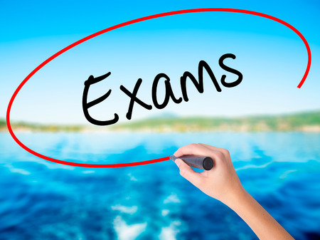 Woman Hand Writing Exams on blank transparent board with a marker isolated over water background. Business concept. Stock Photo