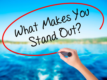 Woman Hand Writing What Makes You Stand Out? on blank transparent board with a marker isolated over water background. Business concept. Stock Photo