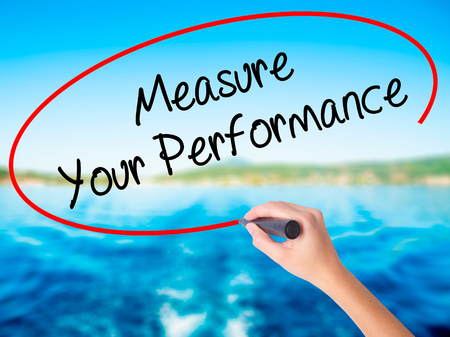Woman Hand Writing Measure Your Performance on blank transparent board with a marker isolated over water background. Business concept. Stock Photo