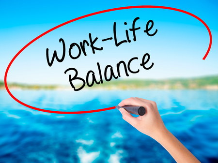Woman Hand Writing Work-Life Balance on blank transparent board with a marker isolated over water background. Business concept. Stock Photo
