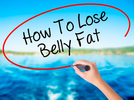 waistline: Woman Hand Writing How To Lose Belly Fat on blank transparent board with a marker isolated over water background. Business concept. Stock Photo