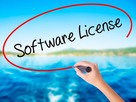 linker: Woman Hand Writing Software License on blank transparent board with a marker isolated over water background. Business concept. Stock Photo