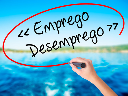 need direction: Woman Hand Writing Emprego Desemprego (Employment - Unemployment in Portuguese)  on blank transparent board with a marker isolated over water background. Business concept. Stock Photo