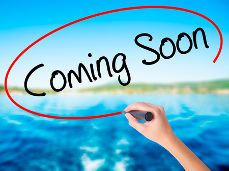 Woman Hand Writing Coming Soon on blank transparent board with a marker isolated over water background. Business concept. Stock Photo
