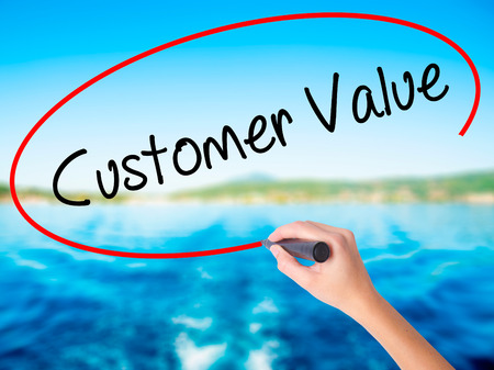 Woman Hand Writing Customer Value on blank transparent board with a marker isolated over water background. Business concept. Stock Photo Stock Photo