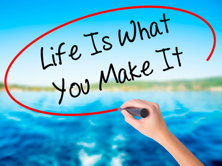 street wise: Woman Hand Writing Life Is What You Make It on blank transparent board with a marker isolated over water background. Business concept. Stock Photo Stock Photo