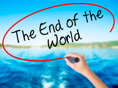 Woman Hand Writing The End of the World on blank transparent board with a marker isolated over water background. Business concept. Stock Photo