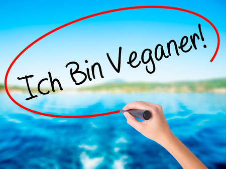 Woman Hand Writing Ich Bin Veganer! (Im Vegetarian in German) on blank transparent board with a marker isolated over water background. Business concept. Stock Photo