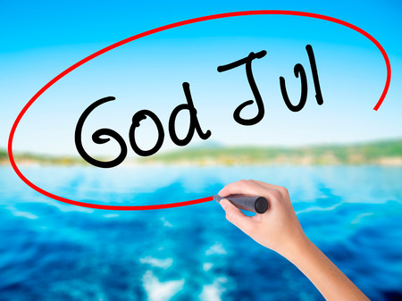 lucia: Woman Hand Writing God Jul  (Merry Christmas in Swedish) on blank transparent board with a marker isolated over water background. Business concept. Stock Photo