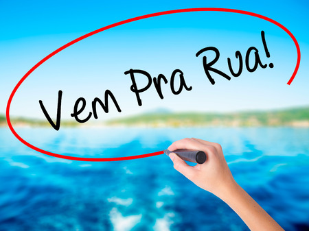 Woman Hand Writing Vem Pra Rua! (Come to Street in Portuguese) on blank transparent board with a marker isolated over water background. Business concept. Stock Photo Stock Photo