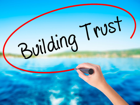 building trust: Woman Hand Writing Building Trust on blank transparent board with a marker isolated over water background. Business concept. Stock Photo