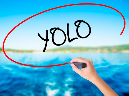 seize: Woman Hand Writing YOLO (You Only Live Once) on blank transparent board with a marker isolated over water background. Business concept. Stock Photo Stock Photo