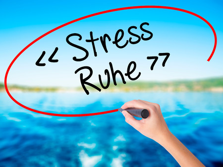 Woman Hand Writing Stress Ruhe  (Stress - Peacein German) on blank transparent board with a marker isolated over water background. Business concept. Stock Photo Stock Photo