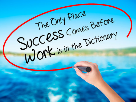 Woman Hand Writing The Only Place Success Comes Before Work is in the Dictionary on blank transparent board with a marker isolated over water background. Business concept. Stock Photo Stock Photo