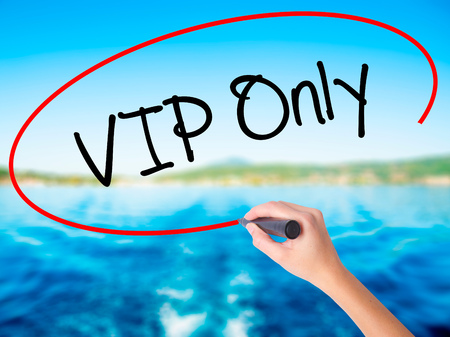 Woman Hand Writing VIP Only   on blank transparent board with a marker isolated over water background. Business concept. Stock Photo
