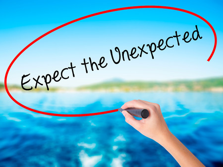 Woman Hand Writing Expect the Unexpected on blank transparent board with a marker isolated over water background. Business concept. Stock Photo Stock Photo