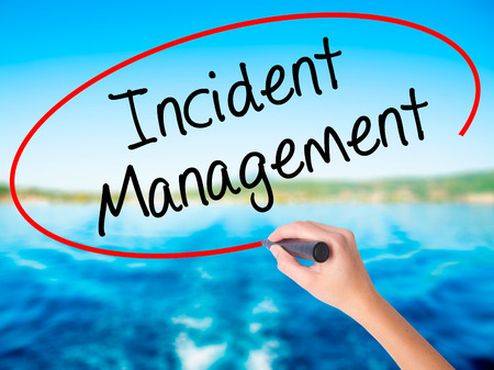 drp: Woman Hand Writing Incident Management on blank transparent board with a marker isolated over water background. Business concept. Stock Photo
