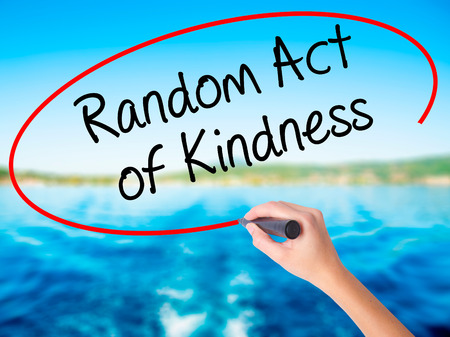 Woman Hand Writing Random Act of Kindness on blank transparent board with a marker isolated over water background. Business concept. Stock Photo