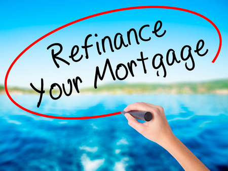 Woman Hand Writing Refinance Your Mortgage on blank transparent board with a marker isolated over water background. Business concept. Stock Photo