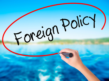 Woman Hand Writing Foreign Policy on blank transparent board with a marker isolated over water background. Business concept. Stock Photo Stock Photo