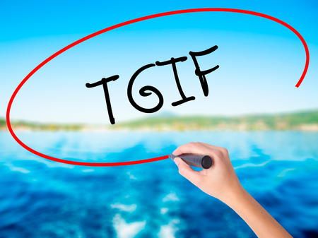 Woman Hand Writing TGIF on blank transparent board with a marker isolated over water background. Business concept. Stock Photo
