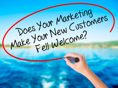 Woman Hand Writing Does Your Marketing Make Your New Customers Fell Welcome?  on blank transparent board with a marker isolated over water background. Business concept. Stock Photo