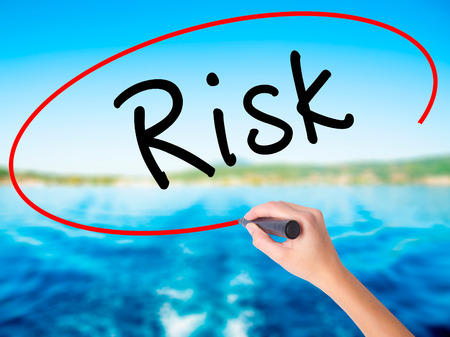 assess: Woman Hand Writing Risk on blank transparent board with a marker isolated over water background. Business concept. Stock Photo
