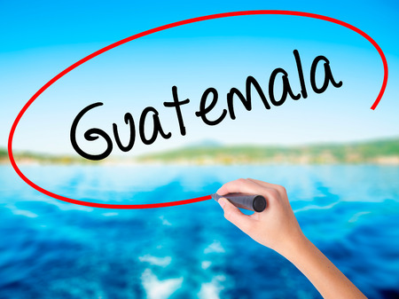 Woman Hand Writing Guatemala  on blank transparent board with a marker isolated over water background. Business concept. Stock Photo