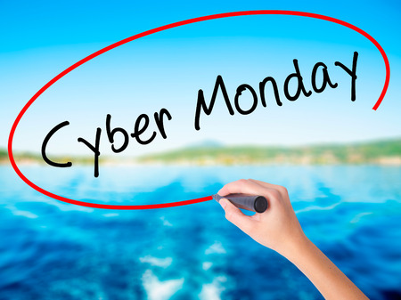 Woman Hand Writing Cyber Monday on blank transparent board with a marker isolated over water background. Business concept. Stock Photo Stock Photo