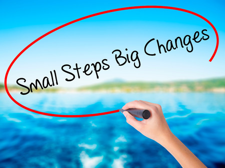 Woman Hand Writing Small Steps Big Changes on blank transparent board with a marker isolated over water background. Business concept. Stock Photo