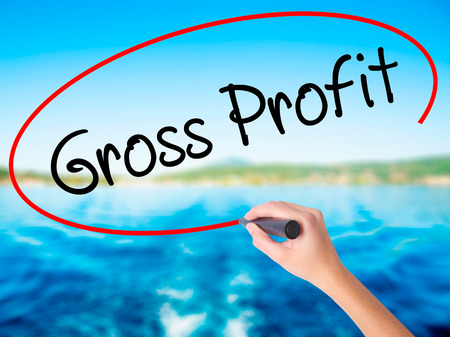Woman Hand Writing Gross Profit on blank transparent board with a marker isolated over water background. Business concept. Stock Photo