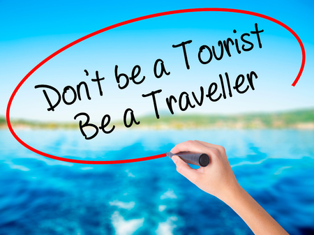 Woman Hand Writing Dont be a Tourist Be a Traveller  on blank transparent board with a marker isolated over water background. Business concept. Stock Photo