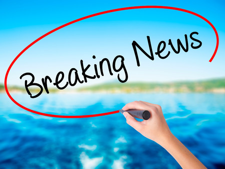 annoucement: Woman Hand Writing Breaking News on blank transparent board with a marker isolated over water background. Business concept. Stock Photo